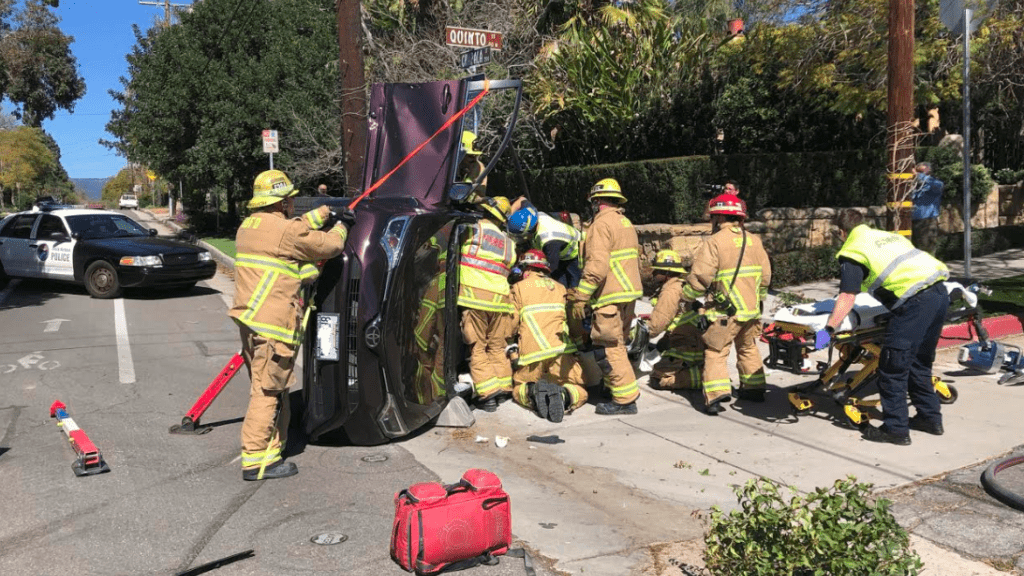 Firefighters work to stabilize vehicle in Santa Barbara before rescuing the two people inside. (SBPD photo)